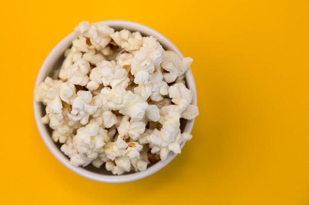 Kom met popcorn op gele achtergrond, thuisbioscoop,