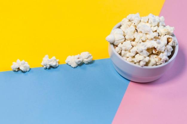 Kom met popcorn op gele, roze en blauwe achtergrond, popcornweg. films, meidenavond