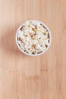 Kom met popcorn op houten tafel. gezinsabonnement voor weekends