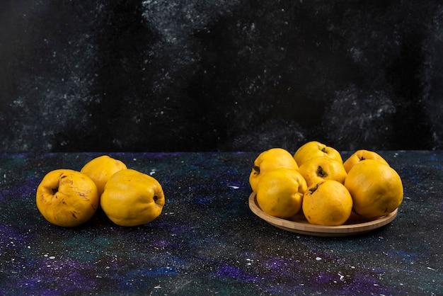 Kom met rijpe kweepeervruchten op donkere tafel geplaatst.