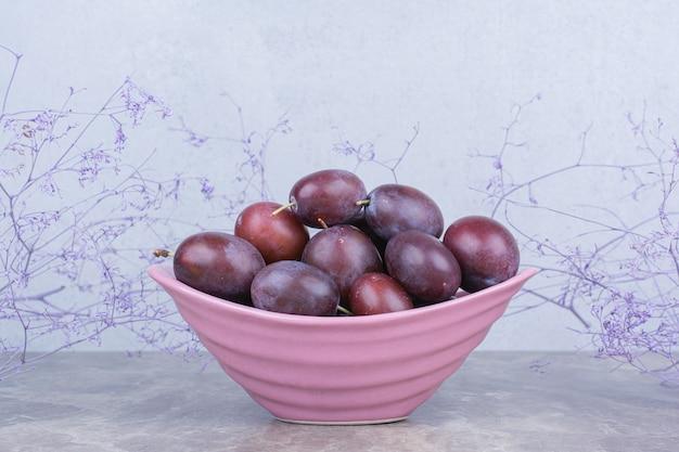 Kom met rijpe pruimen op stenen tafel met planten.
