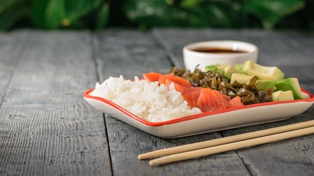 Kom met rijst, avocado, zeewier en zalm op een tafel