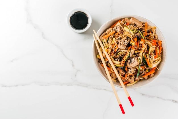 Kom met rijstnoedels met sojasaus en eetstokjes