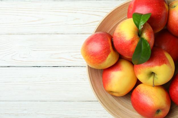 Kom met rode appels op witte houten tafel