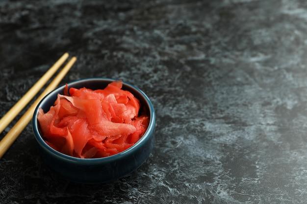 Kom met rode ingelegde gember en eetstokjes op zwarte smokey-oppervlakte