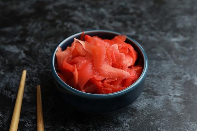 Kom met rode ingelegde gember en eetstokjes op zwarte smokey