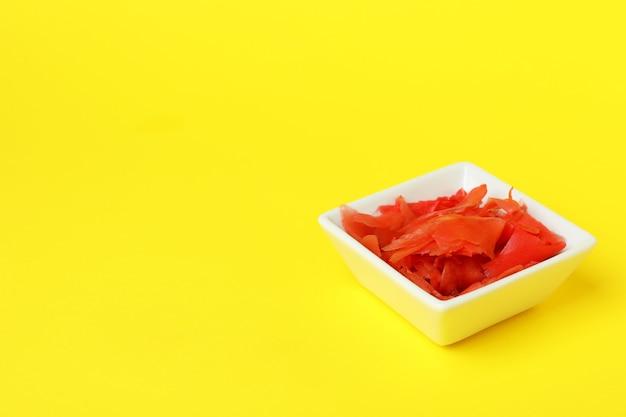 Kom met rode ingelegde gember op geel