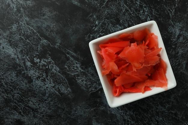 Kom met rode ingelegde gember op zwarte smokey oppervlakte