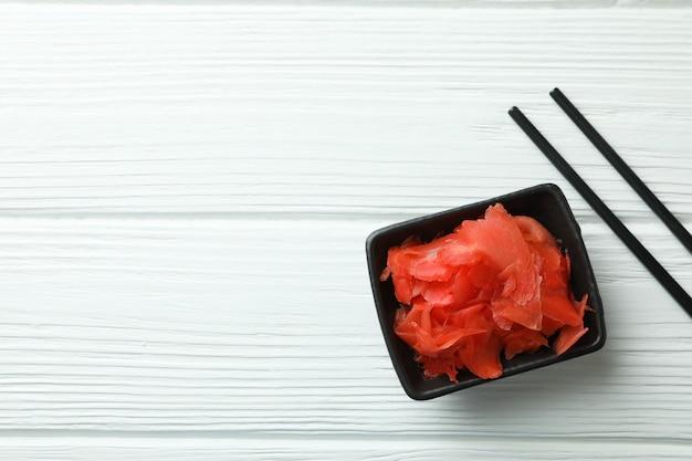 Kom met rode ingemaakte gember en eetstokjes op witte houten oppervlakte