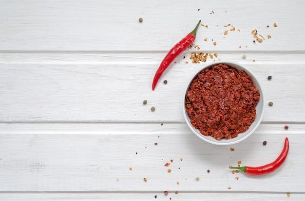 Kom met rode marokkaanse harissa en verse rode chili pepers op witte achtergrond. detailopname