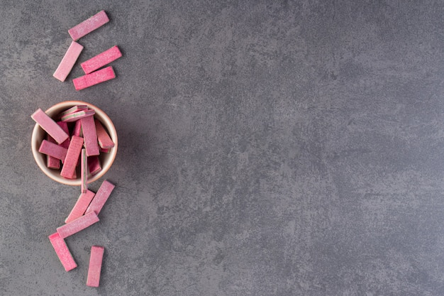 Kom met roze lange kauwgom op stenen tafel.