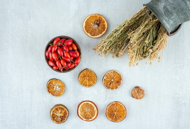 Kom met rozenbottels, gedroogde sinaasappel en wijnruit op stenen oppervlak.
