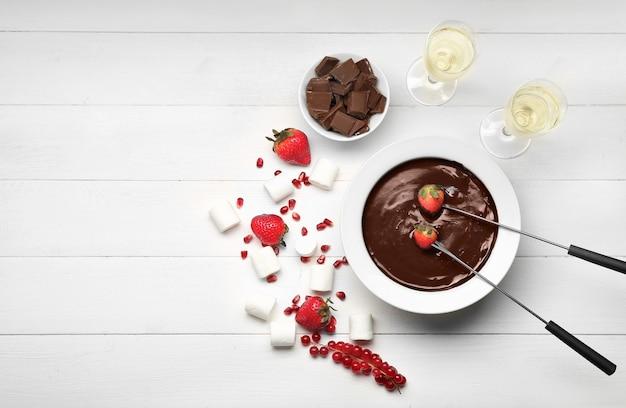Kom met smakelijke chocoladefondue, bessen en marshmallow op tafel