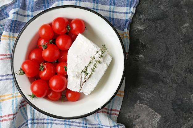 Kom met smakelijke fetakaas en tomaten op grijs