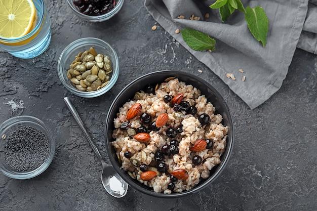 Kom met smakelijke havermout, bessen en noten op grijze tafel