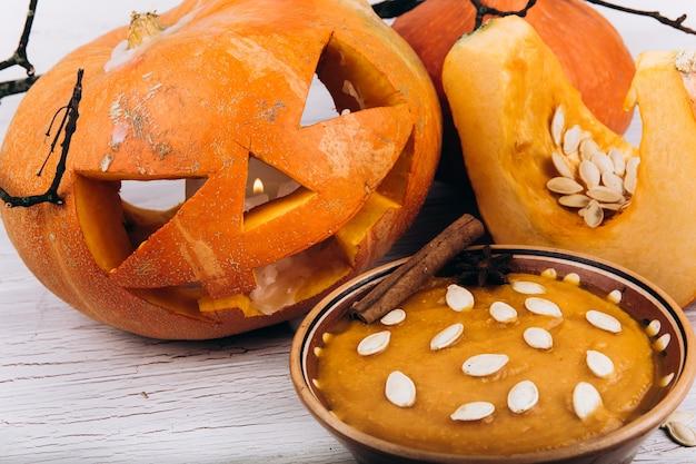 Kom met soep staat voor scarry halloween pompoen op de tafel