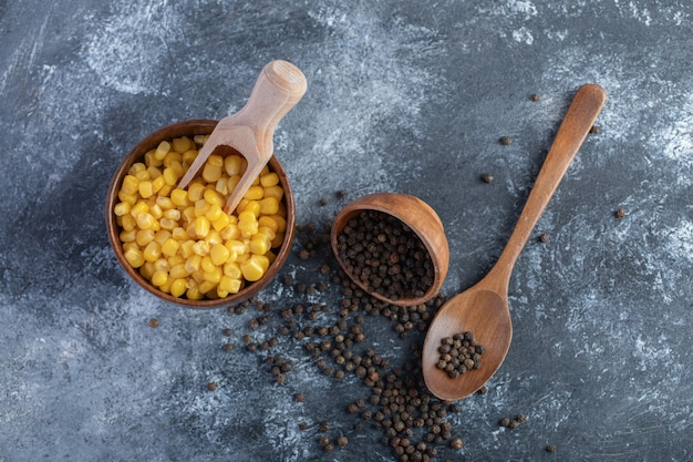 Kom met suikermaïs en graanpaprika's op marmer.