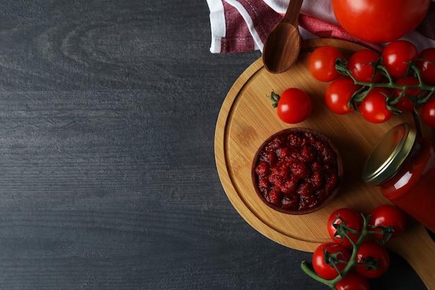 Kom met tomatenpuree op donkere houten tafel met ingrediënten