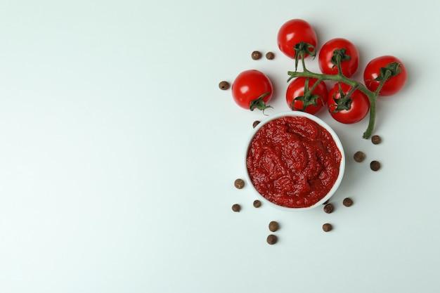 Kom met tomatenpuree, tomaten en zout op witte achtergrond