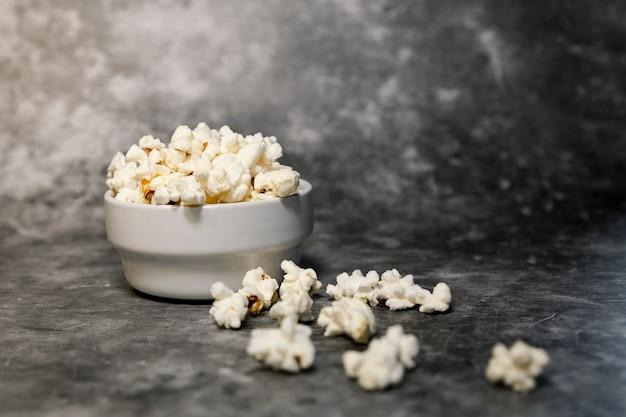 Kom met veel popcorn op grijze achtergrond. weekendplan, thuisbioscoop.