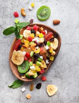 Kom met verschillende gedroogde vruchten en noten op een grijze betonnen ondergrond