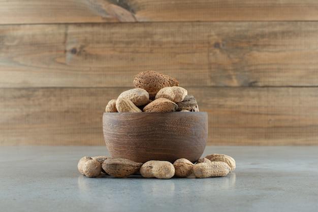 Kom met verschillende noten op marmeren tafel. hoge kwaliteit foto