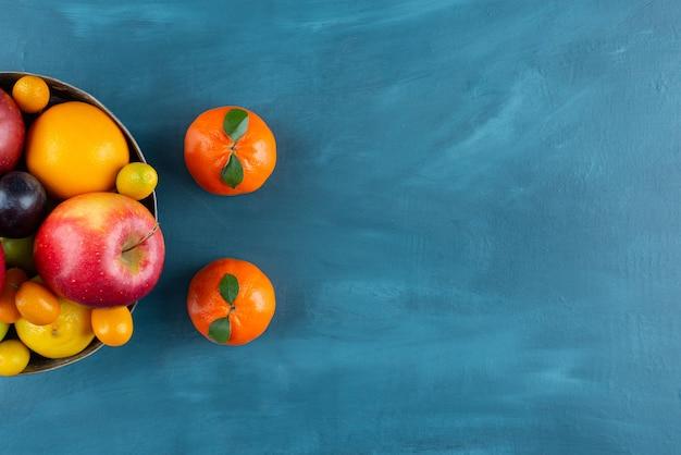 Kom met verschillende soorten vers fruit op blauwe achtergrond.