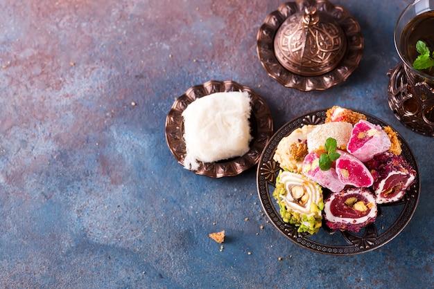 Kom met verschillende stukken turks fruitlokum en zwarte thee met munt