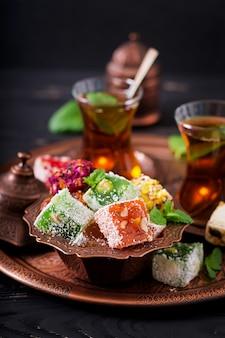 Kom met verschillende stukken van turks fruit lokum en zwarte thee met munt op een donkere tafel