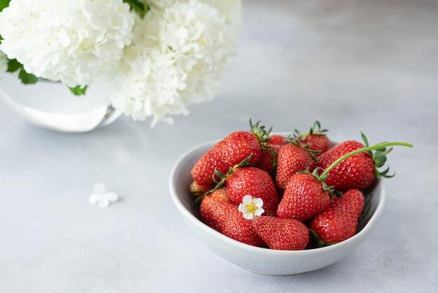 Kom met verse aardbeien en een mooi boeket bos bloemen
