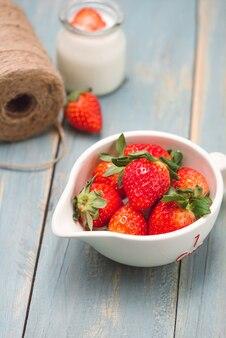 Kom met verse aardbeien op blauwe houten tafel.