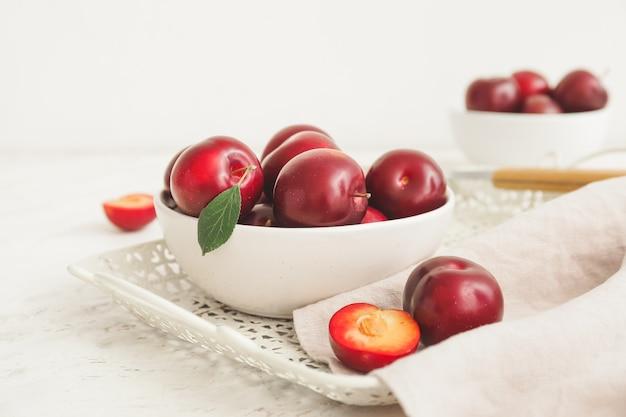 Kom met verse rijpe pruimen op tafel
