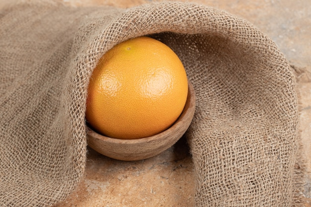 Kom met verse sinaasappel op marmeren oppervlak met jute.
