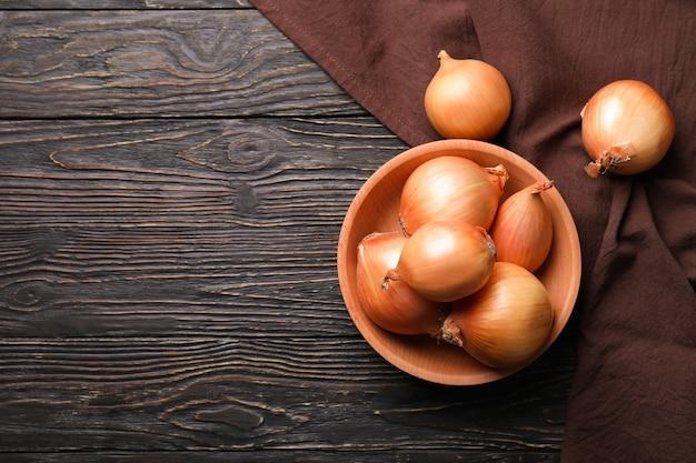 Kom met verse ui en keukenhanddoek op houten achtergrond