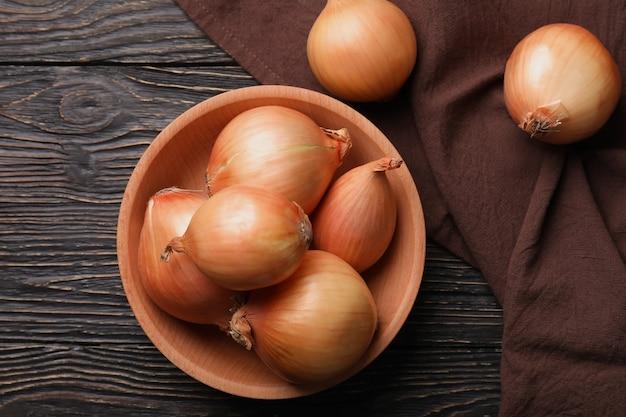 Kom met verse ui en keukenhanddoek op houten