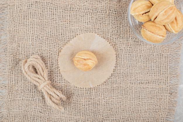 Kom met walnootvormige koekjes in glazen kom op jute. hoge kwaliteit foto