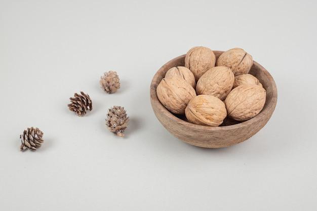 Kom met walnoten en dennenappels op beige oppervlak