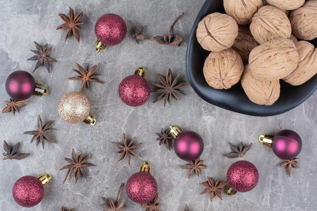 Kom met walnoten met kruidnagel en kerstballen.