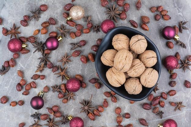 Kom met walnoten met rozebottels en kerstballen.