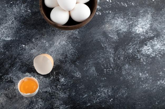 Kom met witte eieren en dooier op marmeren oppervlak.