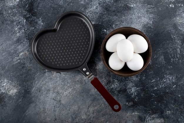 Kom met witte eieren naast hartvormige pan.