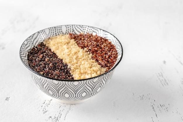 Kom met witte, rode en zwarte gekookte quinoa