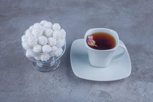 Kom met witte zoete snoepjes met kopje thee op stenen oppervlak.