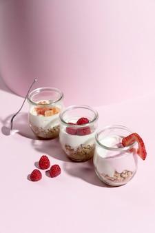 Kom met yougurt met framboos op het bureau