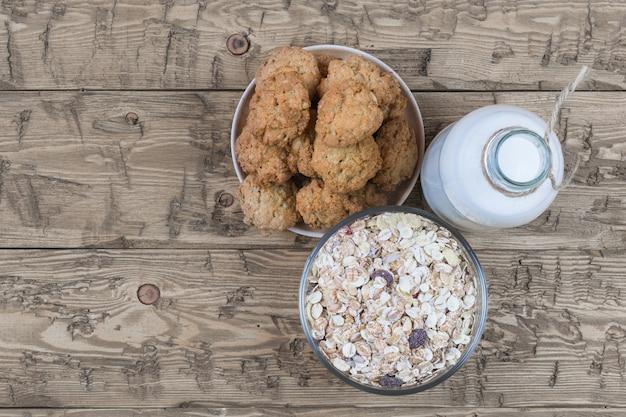 Kom met zelfgemaakte koekjes, fles melk en muesli op bruine houten tafel.
