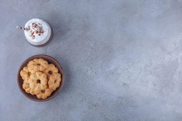 Kom met zoete koekjes met glas koffie op marmeren achtergrond.