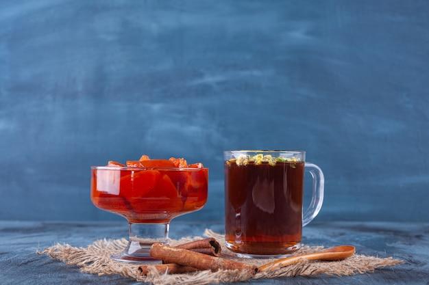 Kom met zoete kweepeerjam en kopje thee op marmeren achtergrond.