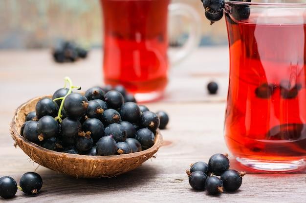 Kom met zwarte bessen en verse compote van rijpe zwarte bessen in een glas op een houten tafel
