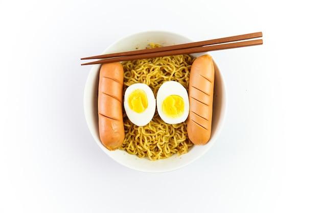 Kom noedels met ei en worst geïsoleerd op witte achtergrond