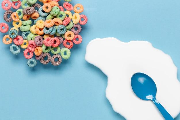 Kom ontbijtgranen en scheutje melk met blauwe lepel